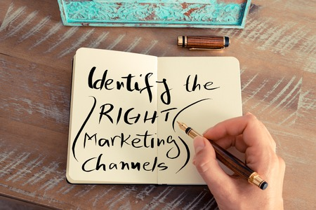 identify: Retro effect and toned image of a woman hand writing a note with a fountain pen on a notebook. Handwritten text IDENTIFY THE RIGHT MARKETING CHANNELS, business success concept