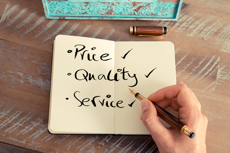 pen quality: Retro effect and toned image of a woman hand writing a note with a fountain pen on a notebook. Handwritten text PRICE QUALITY SERVICE, business success concept