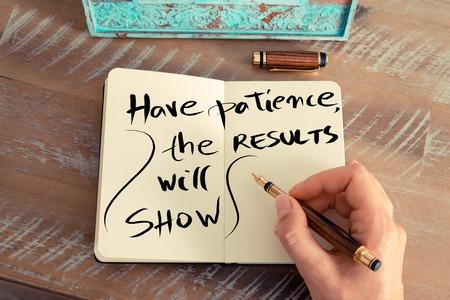 paciencia: efecto retro y la imagen en tonos de la mano de una mujer que escribe una nota con una pluma en un cuaderno. texto escrito a mano tener paciencia, Los resultados mostrarán, el concepto de éxito del negocio Foto de archivo