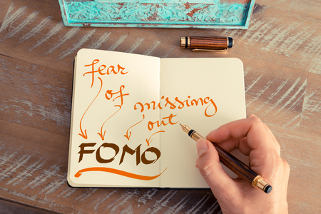 Retro effect and toned image of a woman hand writing a note with a fountain pen on a notebook. Handwritten text FOMO FEAR OF MISSING OUT, business success concept