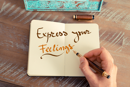 express feelings: Retro effect and toned image of a woman hand writing a note with a fountain pen on a notebook. Handwritten text EXPRESS YOUR FEELINGS, business success concept
