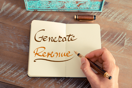 generate: Retro effect and toned image of a woman hand writing a note with a fountain pen on a notebook. Handwritten text GENERATE REVENUE, business success concept