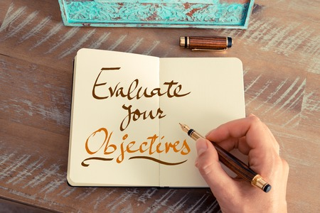 objectives: Retro effect and toned image of a woman hand writing a note with a fountain pen on a notebook. Handwritten text EVALUATE YOUR OBJECTIVES, business success concept
