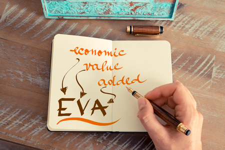 eva: Retro effect and toned image of a woman hand writing a note with a fountain pen on a notebook. Handwritten text EVA ECONOMIC VALUE ADDED, business success concept