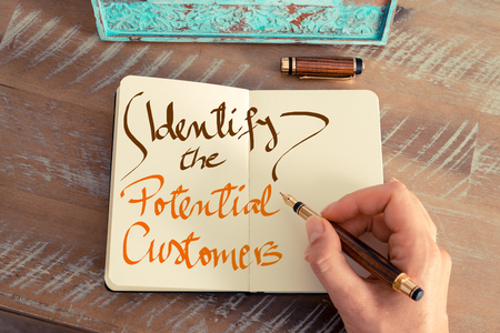 identify: Retro effect and toned image of a woman hand writing a note with a fountain pen on a notebook. Handwritten text IDENTIFY THE POTENTIAL CUSTOMERS, business success concept Stock Photo