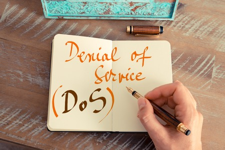 denial: Retro effect and toned image of a woman hand writing a note with a fountain pen on a notebook. Handwritten text DOS DENIAL OF SERVICE, business success concept