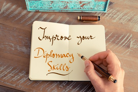 diplomacy: Retro effect and toned image of a woman hand writing a note with a fountain pen on a notebook. Handwritten text IMPROVE YOUR DIPLOMACY SKILLS, business success concept