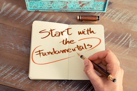 fundamentals: Retro effect and toned image of a woman hand writing a note with a fountain pen on a notebook. Handwritten text  START WITH THE FUNDAMENTALS, business success concept