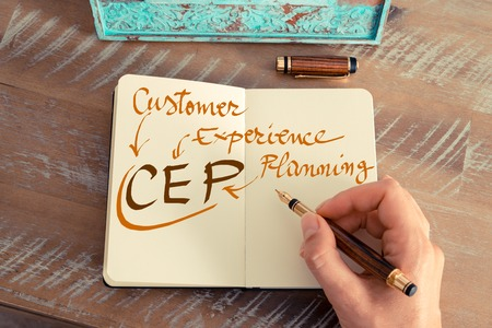 cep: Retro effect and toned image of a woman hand writing a note with a fountain pen on a notebook. Handwritten text CEP Customer Experience Planning, business success concept
