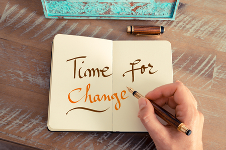 Retro effect and toned image of a woman hand writing a note with a fountain pen on a notebook. Handwritten text TIME FOR CHANGE, success concept