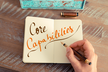 capabilities: Retro effect and toned image of a woman hand writing a note with a fountain pen on a notebook. Handwritten text CORE CAPABILITIES Stock Photo