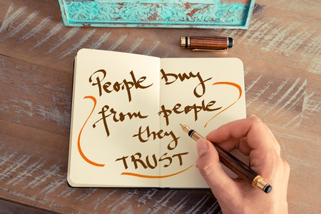 trust people: Retro effect and toned image of a woman hand writing a note with a fountain pen on a notebook. Handwritten text PEOPLE BUY FROM PEOPLE THEY TRUST, business success concept Stock Photo