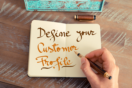define: Retro effect and toned image of a woman hand writing a note with a fountain pen on a notebook. Handwritten text DEFINE YOUR CUSTOMER PROFILE, business success concept Stock Photo