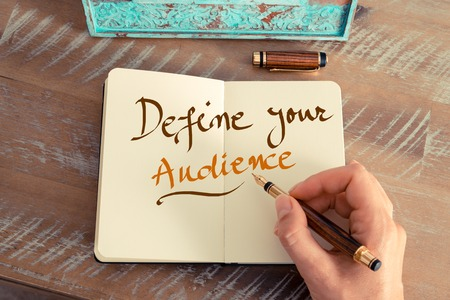 define: Retro effect and toned image of a woman hand writing a note with a fountain pen on a notebook. Handwritten text DEFINE YOUR AUDIENCE, business success concept