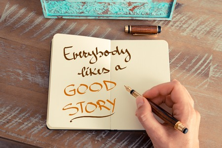 everybody: Retro effect and toned image of a woman hand writing a note with a fountain pen on a notebook. Handwritten text EVERYBODY LIKES A GOOD STORY, business success concept Stock Photo