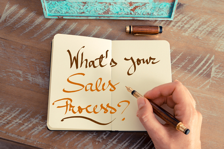 sales process: Retro effect and toned image of a woman hand writing a note with a fountain pen on a notebook. Handwritten text WHATS YOUR SALES PROCESS ?, business success concept