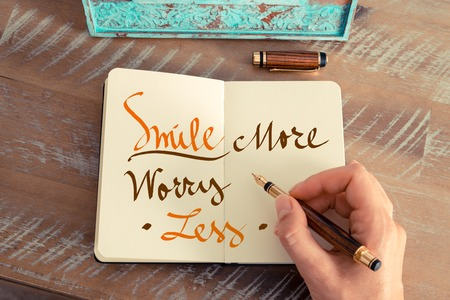 frame less: Retro effect and toned image of a woman hand writing a note with a fountain pen on a notebook. Handwritten text SMILE MORE WORRY LESS, happiness concept Stock Photo