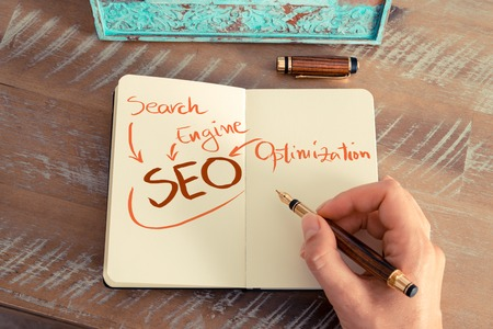 seo concept: Retro effect and toned image of a woman hand writing a note with a fountain pen on a notebook. Handwritten text SEO as SEARCH ENGINE OPTIMIZATION, business success concept