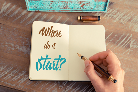 Retro effect and toned image of a woman hand writing a note with a fountain pen on a notebook. Handwritten text WHERE DO I START ?, motivation concept