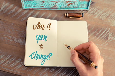 Retro effect and toned image of a woman hand writing a note with a fountain pen on a notebook. Handwritten text AM I OPEN TO CHANGE ?, motivation concept