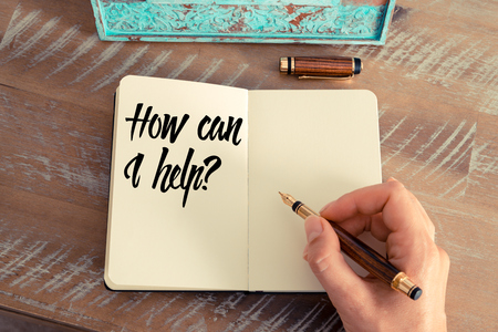 Retro effect and toned image of a woman hand writing a note with a fountain pen on a notebook. Handwritten text HOW CAN I HELP ?, motivation concept