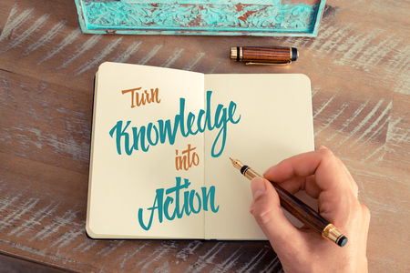 Retro effect and toned image of a woman hand writing a note with a fountain pen on a notebook. Handwritten text TURN KNOWLEDGE INTO ACTION, motivation concept Imagens