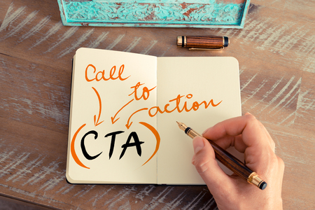 Retro effect and toned image of a woman hand writing a note with a fountain pen on a notebook. Handwritten Business Acronym CTA CALL TO ACTION, motivation concept Standard-Bild