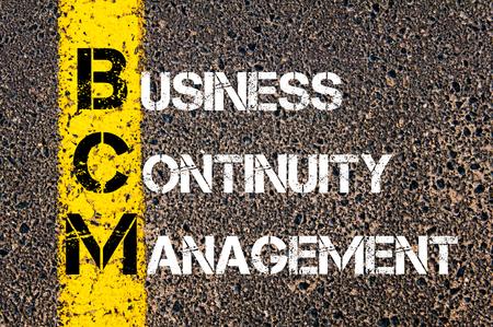 道路標示黄色塗装ライン上に書かれたビジネス頭字語 BCM 事業継続マネジメントのコンセプト イメージ