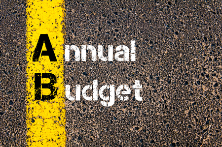 road marking: Concept image of Business Acronym AB Annual Budget written over road marking yellow paint line.