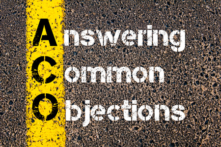 objections: Concept image of Business Acronym ACO Answering Common Objections written over road marking yellow paint line. Stock Photo