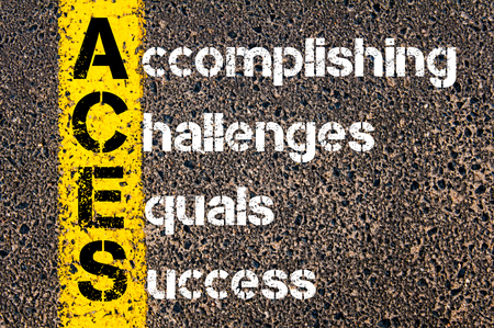 equals: Concept image of Business Acronym ACES Accomplishing Challenges Equals Success written over road marking yellow paint line.