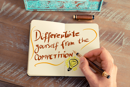 differentiate: Retro effect and toned image of a woman hand writing a note with a fountain pen on a notebook. Handwritten text DIFFERENTIATE YOURSELF FROM THE COMPETITION next to yellow lighting bulb.