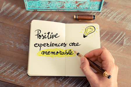 memorable: Retro effect and toned image of a woman hand writing a note with fountain pen on a notebook. Handwritten text Positive Experiences Are Memorable next to yellow lighting bulb as symbol for bright idea.