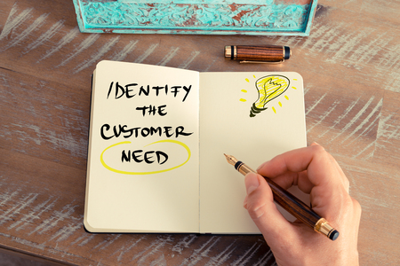 identify: Retro effect and toned image of a woman hand writing a note with a fountain pen on a notebook. Handwritten text IDENTIFY THE CUSTOMER NEED next to yellow lighting bulb as symbol for bright idea. Stock Photo