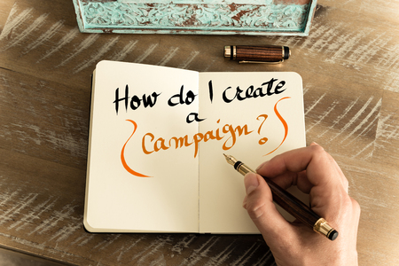 Retro effect and toned image of a woman hand writing a note with a fountain pen on a notebook. Handwritten text HOW DO I CREATE A CAMPAIGN ?, motivation concept