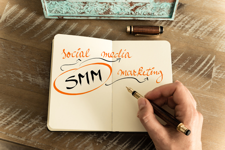 smm: Retro effect and toned image of notebook next to a fountain pen. Business acronym SMM as SOCIAL MEDIA MARKETING with handwritten text