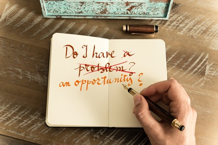 Retro effect and toned image of a woman hand writing a note with a fountain pen on a notebook. Handwritten text DO I HAVE AN OPPORTUNITY ? word PROBLEM cut with red line, motivation concept Banco de Imagens