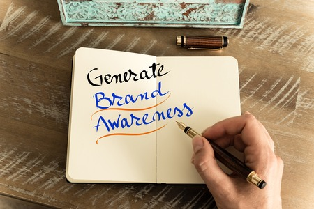 generate: Retro effect and toned image of a woman hand writing a note with a fountain pen on a notebook. Handwritten text GENERATE BRAND AWARENESS, motivation concept