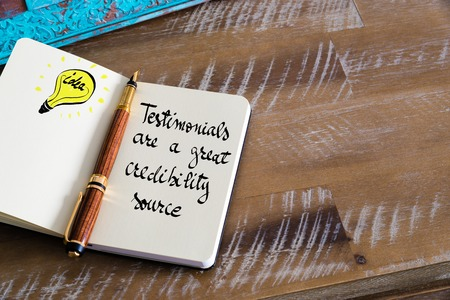 credibility: Retro effect and toned image of notebook next to a fountain pen. Business concept image with handwritten text TESTIMONIALS ARE A GREAT CREDIBILITY SOURCE, copy space available, light bulb as idea