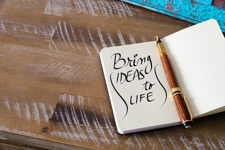 the next life: Retro effect and toned image of notebook next to a fountain pen. Business concept image with handwritten text BRING IDEAS TO LIFE , copy space available