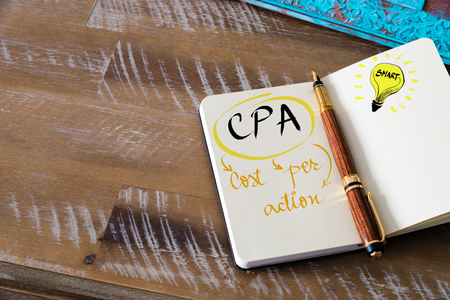 cpa: Retro effect and toned image of notebook next to a fountain pen. Business acronym CPA COST PER ACTION with handwritten text