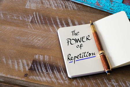 repetition: Retro effect and toned image of notebook next to a fountain pen. Business concept image with handwritten text THE POWER OF REPETITION , copy space available Stock Photo