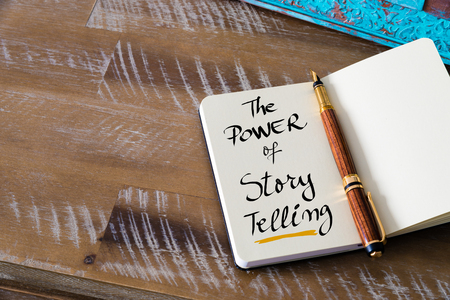 relations: Retro effect and toned image of notebook next to a fountain pen. Business concept image with handwritten text THE POWER OF STORY TELLING , copy space available