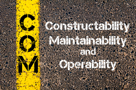 maintainability: Concept image of Business Acronym COM Constructability, Maintainability, and Operability written over road marking yellow paint line