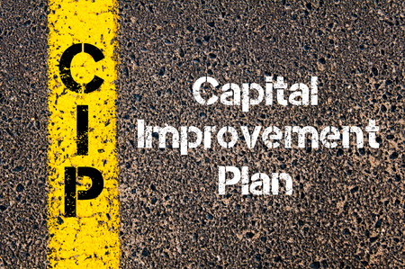 road marking: Concept image of Business Acronym CIP Capital Improvement Plan written over road marking yellow paint line
