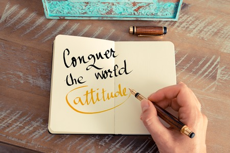 conquer: Retro effect and toned image of a woman hand writing a note with a fountain pen on a notebook. Handwritten text Conquer The World Attitude as lifestyle concept image