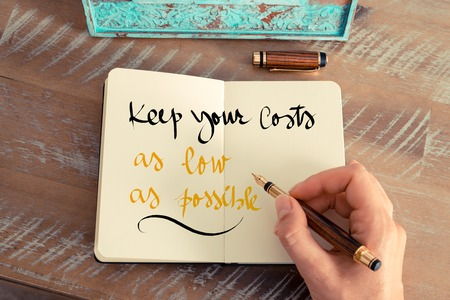 keep your hands: Retro effect and toned image of a woman hand writing a note with a fountain pen on a notebook. Handwritten text Keep Your Costs As Low As Possible as business concept image