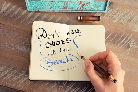 hand wear: Retro effect and toned image of a woman hand writing a note with a fountain pen on a notebook. Handwritten text Dont Wear Shoes At The Beach as lifestyle concept image Stock Photo