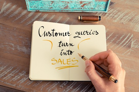 queries: Retro effect and toned image of a woman hand writing a note with a fountain pen on a notebook. Handwritten text Customer Queries Turn Into Sales as business concept image Stock Photo