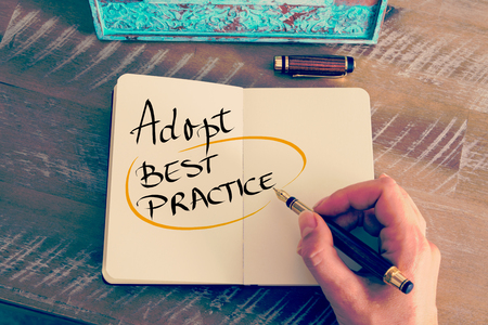 best practices: Retro effect and toned image of a woman hand writing a note with a fountain pen on a notebook. Handwritten text Adopt Best Practice as business concept image